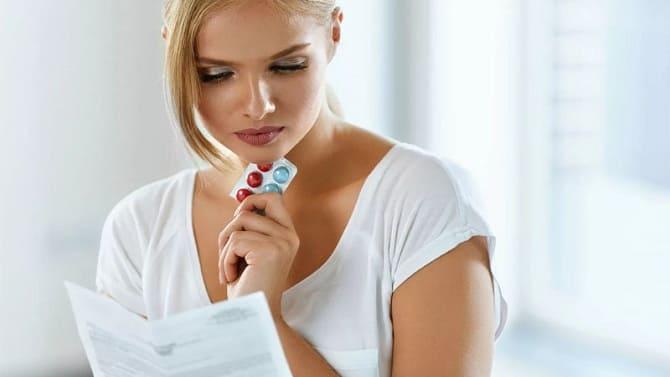 Девушка читает инструкцию к таблеткам